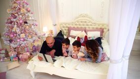 La famille heureuse passent le temps ensemble derrière l'ordinateur portable, se trouvant sur le lit dans la chambre à coucher lu banque de vidéos