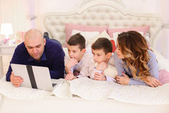 La famille heureuse passent le temps ensemble derrière l'ordinateur portable, se trouvant sur le lit dedans Photos libres de droits