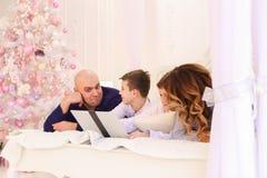 La famille heureuse passent le temps ensemble derrière l'ordinateur portable, se trouvant sur le lit dedans Images stock
