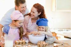La famille heureuse a plaisir cuire au four à faire ensemble Images libres de droits