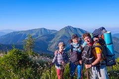 La famille heureuse, randonneurs détendent et appréciant la vie sur le meado alpin Photos stock