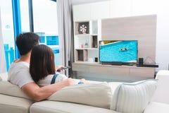 La famille heureuse regarde la télévision tout en se reposant sur le sofa Images stock