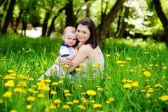 La famille heureuse s'asseyant dehors dans un domaine de pissenlit fleurit Photographie stock libre de droits