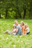 La famille heureuse s'assied dans le jardin Photographie stock libre de droits
