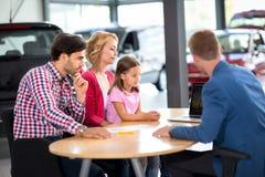 La famille intéressée à acheter la nouvelle voiture écoute agent de voiture Images libres de droits