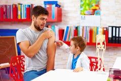 La famille jouant dans le docteur et le patient, père a effrayé de l'injection photo stock