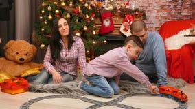 La famille joue sous l'arbre de Noël avec le chemin de fer clips vidéos