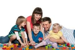 La famille jouent avec des enfants sur le plancher Image libre de droits