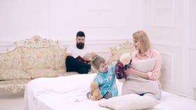 La famille a l'amusement jouant avec des jouets et des oreillers dans le lit Le concept d'une famille heureuse banque de vidéos