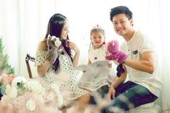 La famille, l'enfant et le concept à la maison - parents de sourire et peu Photo stock