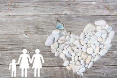 La famille lesbienne sur le fond en bois avec le blanc lapide le coeur et le papillon bleu Image stock