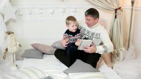 La famille lisant un livre, père affectueux lit un livre à son fils, tout en passant le temps ensemble, un enfant, un petit garço banque de vidéos