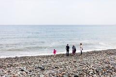 La famille marche le long de la plage par la mer Vent sur le bord de la mer avec des personnes marchant sur la plage Plage rocheu photos stock