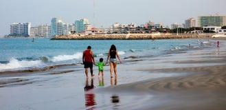 La famille marche sur la plage, avec des salines, horizon de l'Equateur dans le dos Photos libres de droits