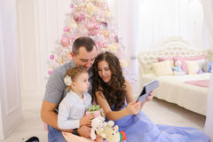 La famille moderne parle avec des parents sur Skype dans la chambre à coucher spacieuse Images libres de droits