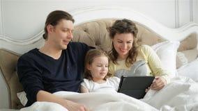 La famille moderne utilise l'instrument électronique se trouvant sur le lit ensemble L'homme bel, la femme de brune et la petite  banque de vidéos