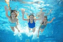 La famille nage dans la piscine sous l'eau, mère active heureuse et les enfants ont l'eau du fond d'amusement, sport d'enfants Photos libres de droits