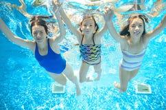 La famille nage dans la piscine sous l'eau, mère active heureuse et les enfants ont l'eau du fond d'amusement, sport d'enfants Photo libre de droits