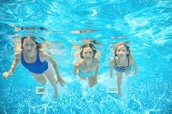 La famille nage dans la piscine sous l'eau, mère active heureuse et les enfants ont l'eau du fond d'amusement, sport d'enfants Images libres de droits