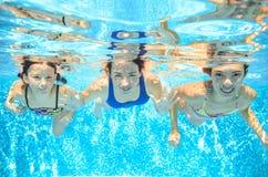 La famille nage dans la piscine sous-marine, mère active heureuse et les enfants ont l'amusement Photographie stock
