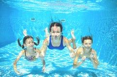 La famille nage dans la piscine sous-marine, mère active heureuse et les enfants ont l'amusement Photo libre de droits