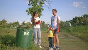 La famille nettoie la nature, portrait de jeunes volontaires heureux père et la mère avec la petite fille rassemble des déchets d banque de vidéos