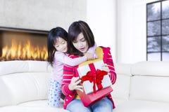 La famille ouvrent un cadeau de Noël sur le sofa Image libre de droits