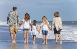 La famille Parents des enfants de fille marchant sur la plage Image libre de droits