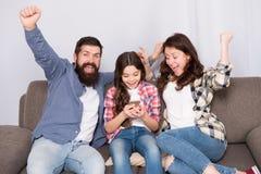 La famille passent le week-end ensemble Smartphone d'utilisation de petite fille d'enfant avec des parents Famille amicale ayant  photos libres de droits
