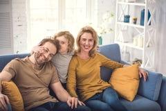 La famille pleine d'adoration détendent dans le confort simple Photographie stock