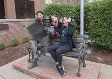 La famille posant humoristique avec le bronze Rogers sur un banc, Claremore, l'Oklahoma Photographie stock