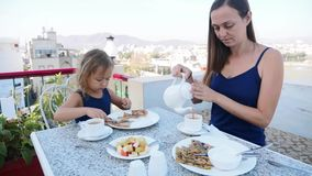 La famille prennent un petit d?jeuner ensemble sur la terrasse avec le beau Mountain View clips vidéos