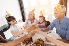 La famille s'assied à une table et aux verres de tintement à l'anniversaire d'une petite fille Photo stock