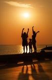 La famille salue le lever de soleil Image stock