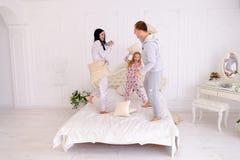 La famille sautant et dupant autour dans le lit, le mari et l'épouse combattent photos stock