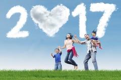 La famille sautent sur le pré avec le nuage 2017 Image libre de droits