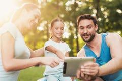 La famille se repose en parc après avoir joué des sports Ils regardent quelque chose sur le comprimé Photographie stock libre de droits