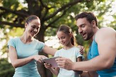 La famille se repose en parc après avoir joué des sports Ils regardent quelque chose sur le comprimé Images stock