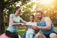 La famille se repose en parc après avoir joué des sports Ils regardent quelque chose sur le comprimé Photographie stock