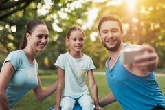 La famille se repose en parc après avoir joué des sports Un homme fait le selfie avec sa famille Photo libre de droits