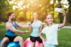 La famille se repose en parc après avoir joué des sports Une fille fait le selfie avec sa famille Photographie stock libre de droits