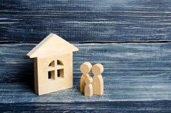La famille se tient près de la maison Les chiffres en bois des personnes se tiennent près d'une maison en bois Le concept d'un co Photographie stock libre de droits