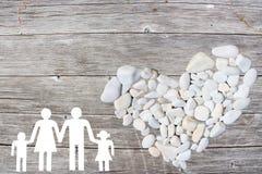 La famille sur le fond en bois avec le blanc lapide le coeur Photos libres de droits