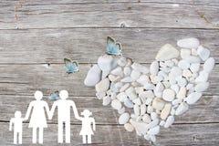 La famille sur le fond en bois avec le blanc lapide le coeur et les papillons bleus Photographie stock