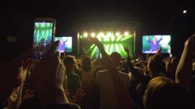 La fan avec le téléphone portable dans des mains fait la vidéo du concert de rock vivant parmi la foule contre la scène brillamme banque de vidéos