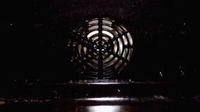 La fan blanca está haciendo girar en el horno almacen de metraje de vídeo