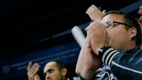 La fan de hockey de la cámara lenta en manos de las palmadas de los vidrios en arena se coloca almacen de video