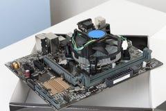 La fan del refrigerador de la CPU está instalando en la placa madre nueva, moderna Foto de archivo
