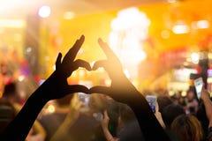 La fan a fait les mains en forme de coeur avec des lumières dans le concert de musique Image stock