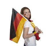 La fan femenina atractiva muestra la bandera alemana y sonríe delante del fondo blanco Imagenes de archivo